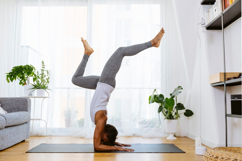 A person does yoga in her living room. You can work out at home even if you're socially distancing with free livestream workouts and exercise app free trials.