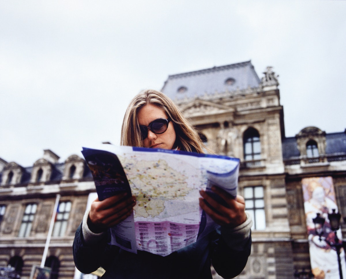 A young woman stands outside the Louvre in Paris with a map.