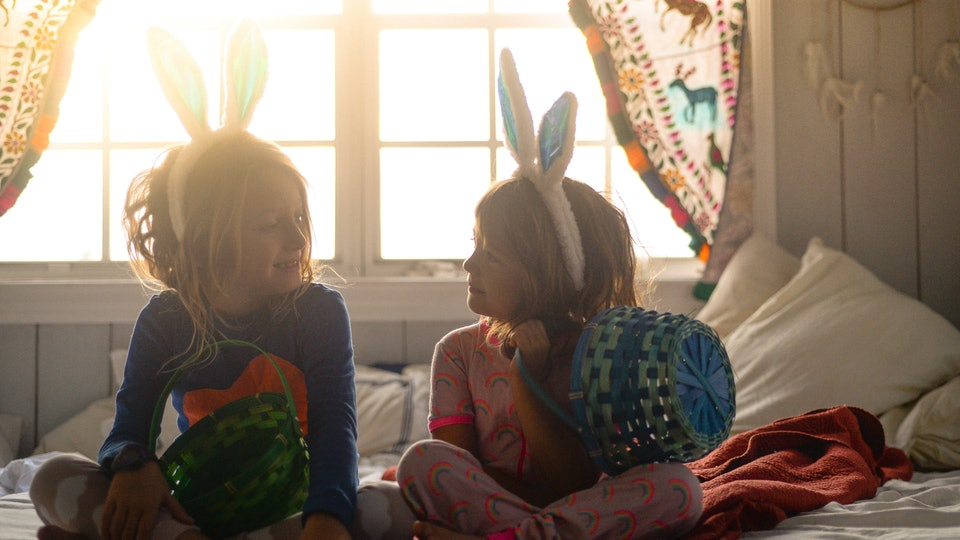two sisters sitting on bed with easter baskets and bunny ears