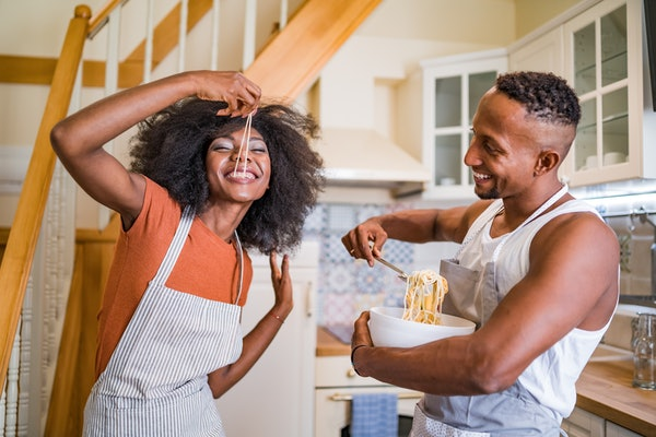 A young couple laughs and eats pasta in their kitchen.