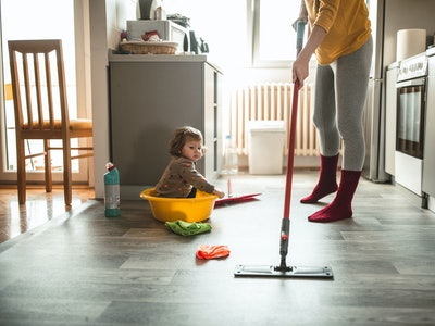 woman cleaning floor with baby watching