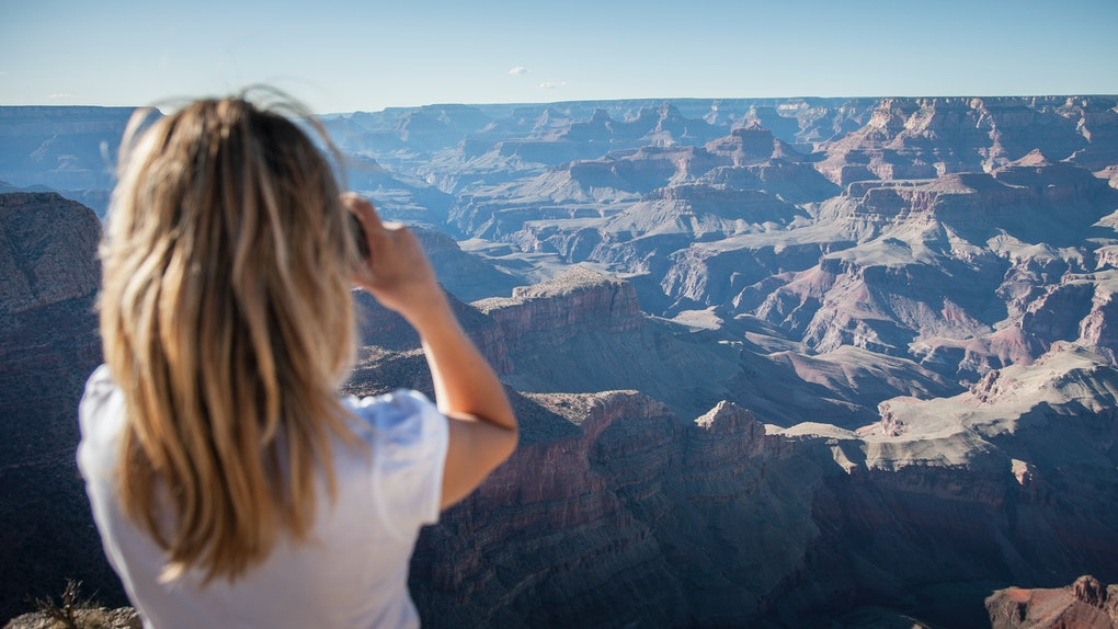 A blonde woman takes a picture of the Grand Canyon while visiting the national park.