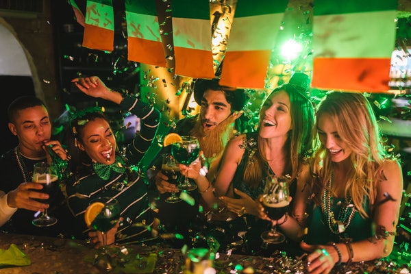 A group of friends dressed up in festive attire for St. Patrick's Day toast their drinks at a bar while confetti falls from the ceiling.