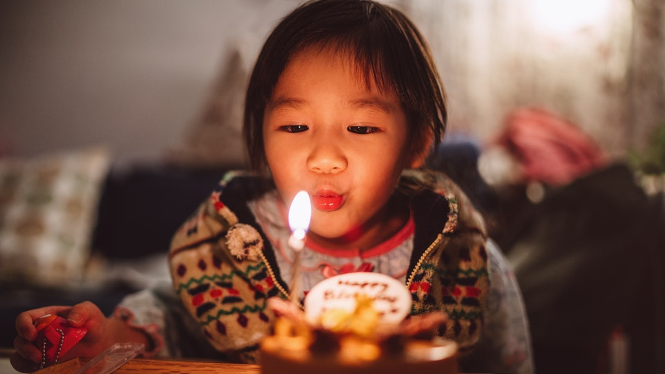 little girl blowing out her birthday candle