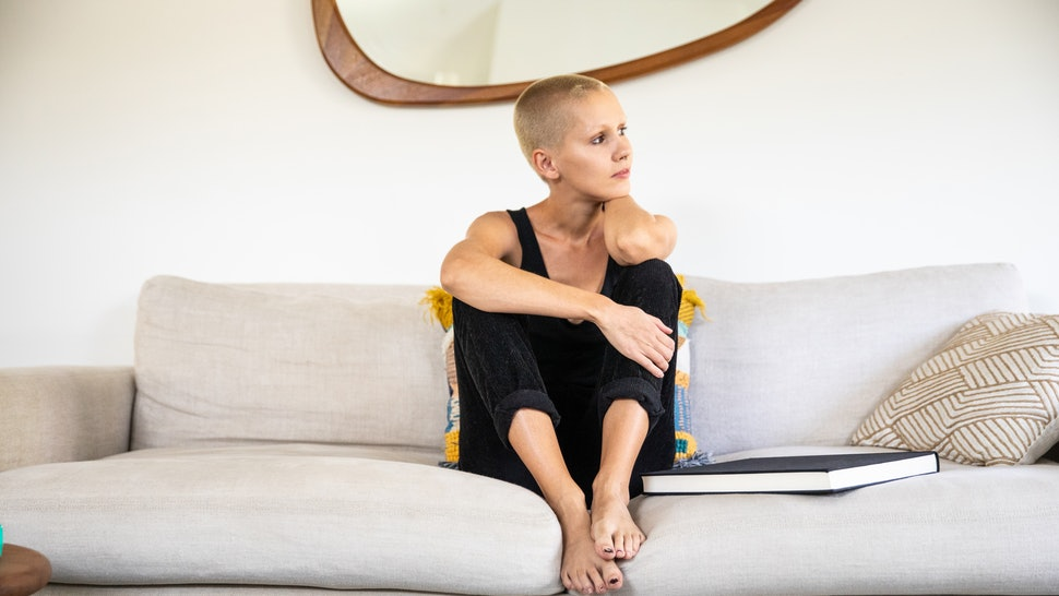 A woman with a shaved head sits on her couch at home. If you need to calm down quickly, these expert hacks can help