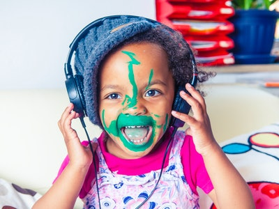 toddler singing with headphones and green paint on face