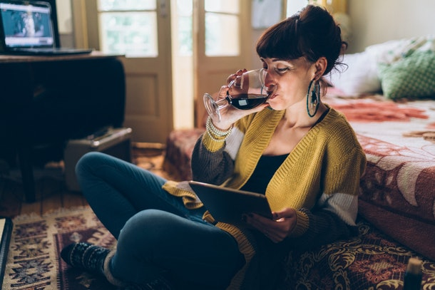 A woman sips her wine while on a virtual call in her home.