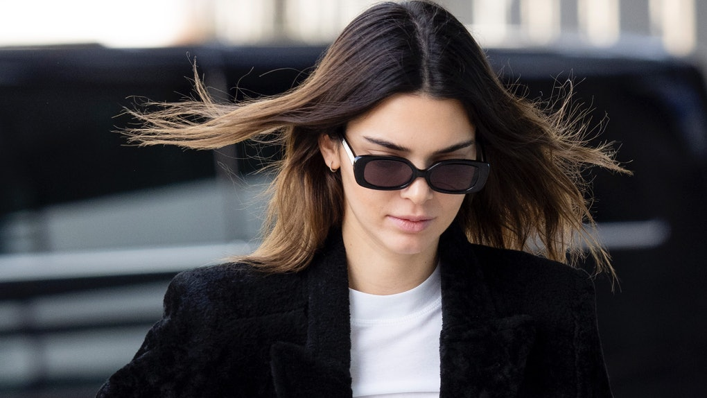 Kendall Jenner steps out in a black coat and matching shades.