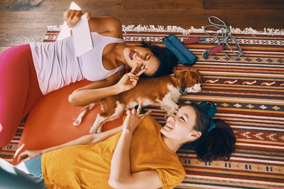 Two friends lay on the floor with their dog while video chatting their friends.