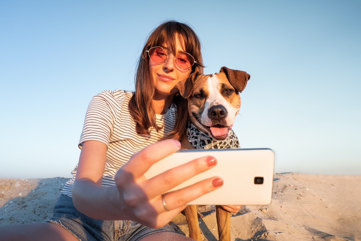 A young woman in pink sunglasses poses for a selfie on the beach with her dog.