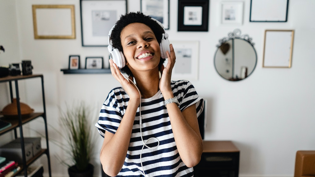 A young woman smiles while listening to music and working from home.