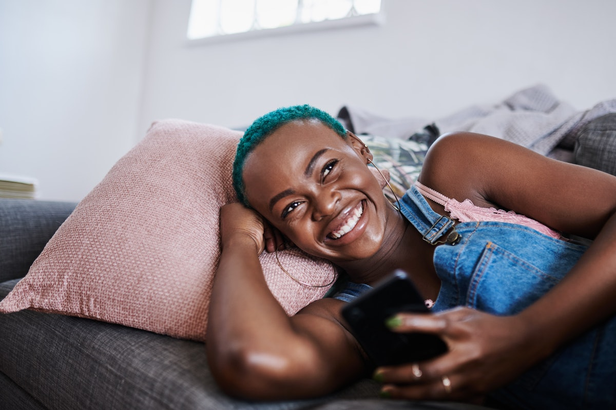 A young woman laughs while holding her phone and thinking on the couch.