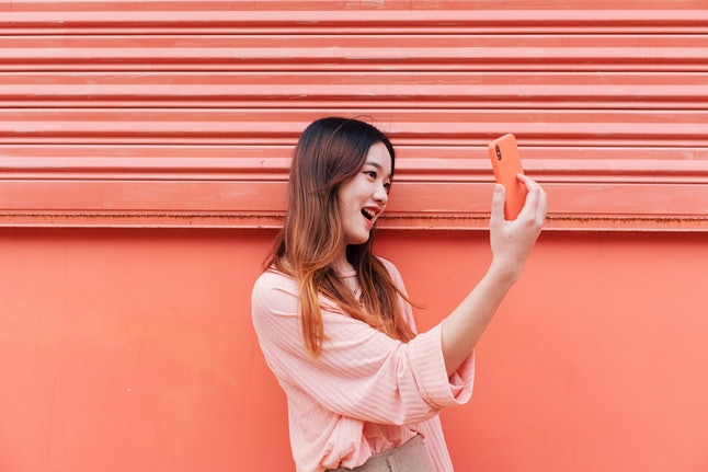 A woman video chats with somebody. Exposure to the faces of others activates a particular part of our brains, and can also boost our moods.