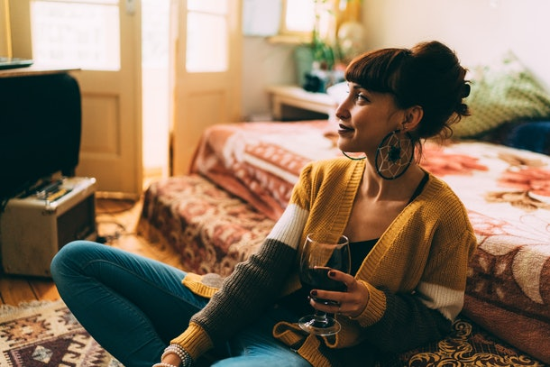 An artsy woman sits in her room with a glass of red wine.