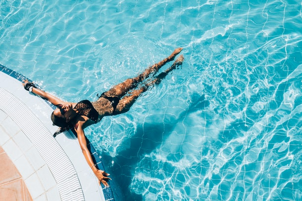 A young woman lounges in the pool of a hotel.