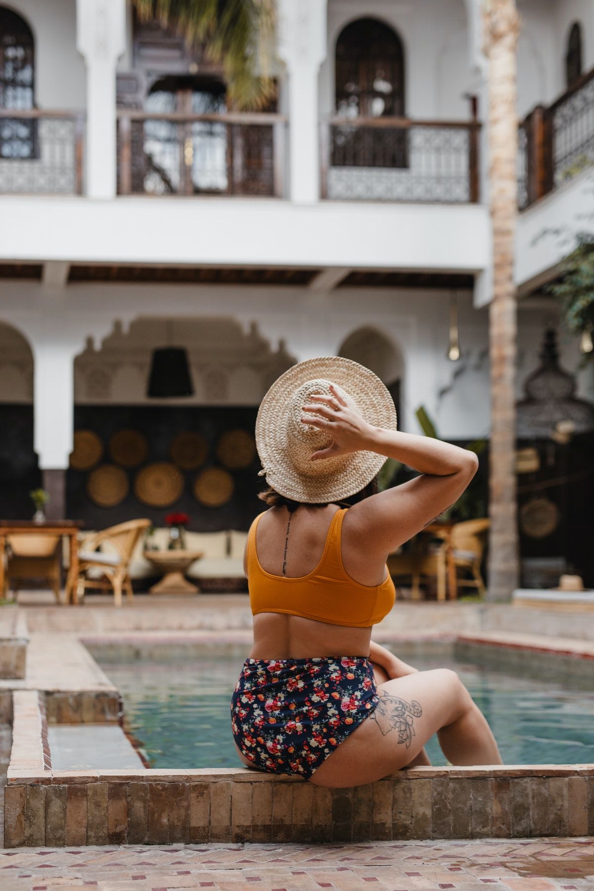 A young woman poses by a hotel's pool in a bathing suit and straw hat.