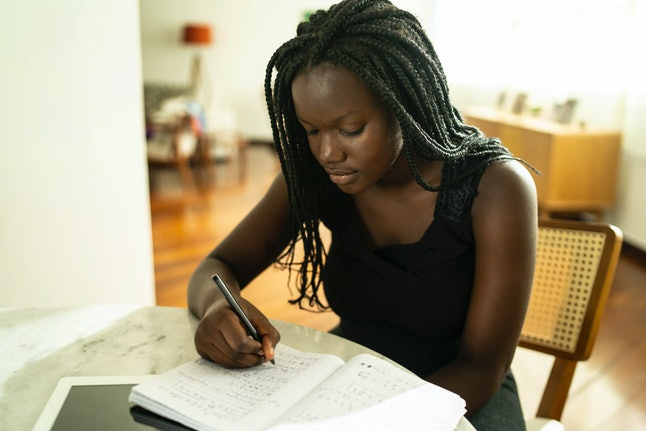 A woman does paperwork. Sticking to a routine while at home helps the brain in various ways.