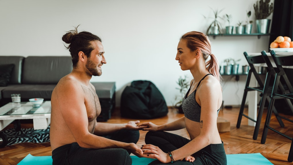 A young couple does yoga in their apartment on a bright blue mat.