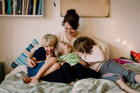 a mom and her kids snuggling on a bed