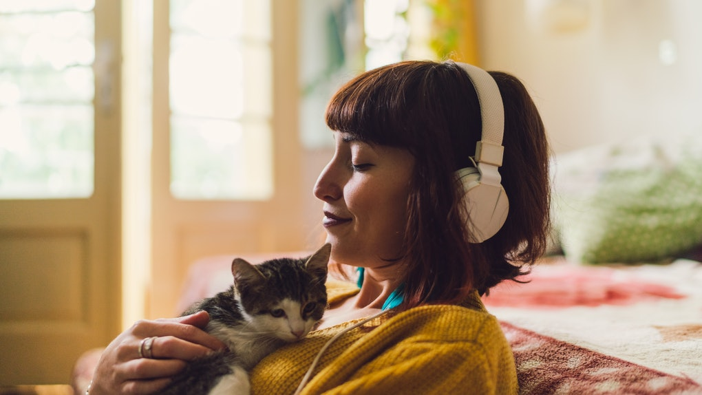 A woman sits in her bedroom and listens to guided meditation while holding her kitten.