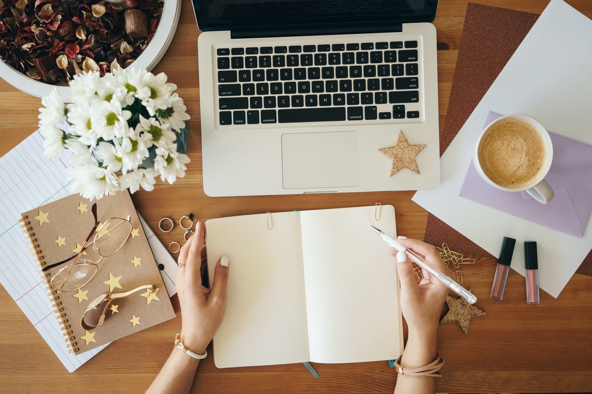 A woman sits with her journal, laptop, and coffee, while working from home.