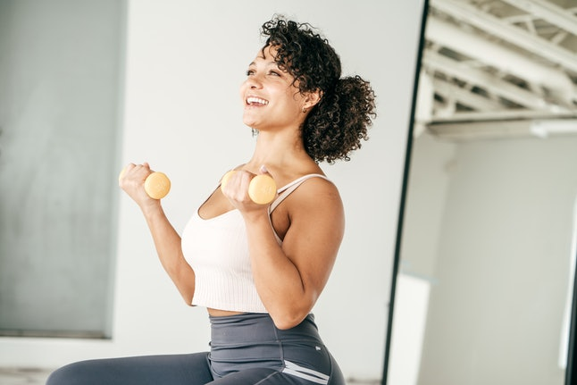 A woman does bicep curls at home. Your brain reacts to at-home workouts similarly to a regular workout.