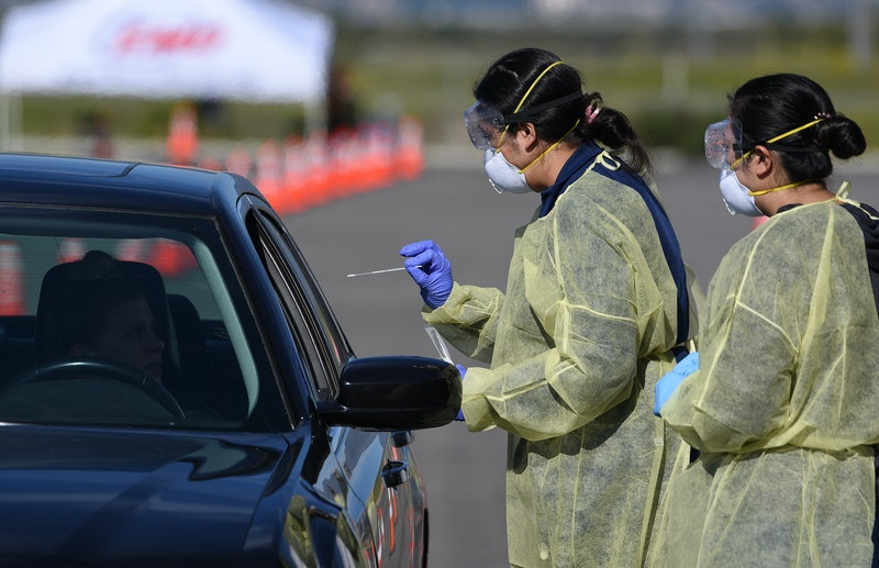 Two workers in PPE administer COVID-19 tests in a drive through testing facility.