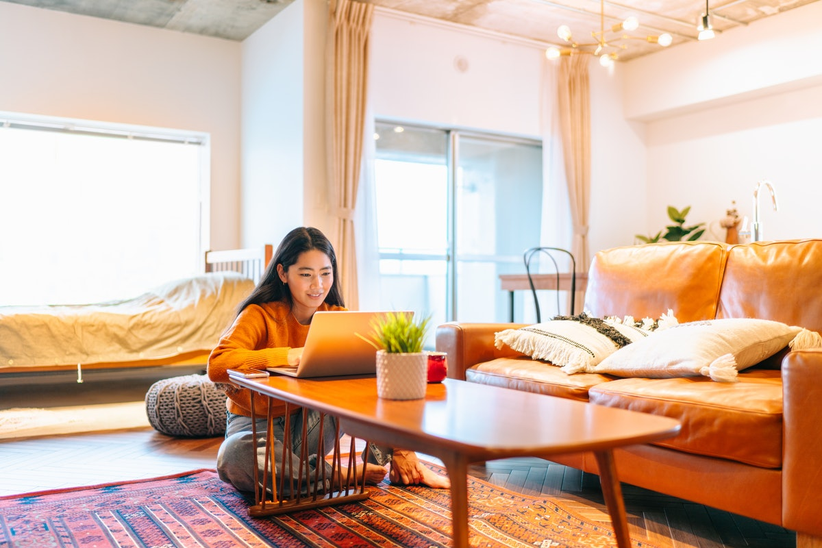 A young woman sits next to her coffee table with her laptop while working from home.