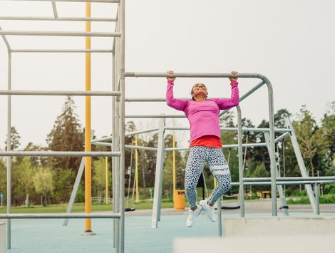 A person smiles as she does pullups in a jungle gym. High-energy workouts can help reduce your anxiety, experts say.