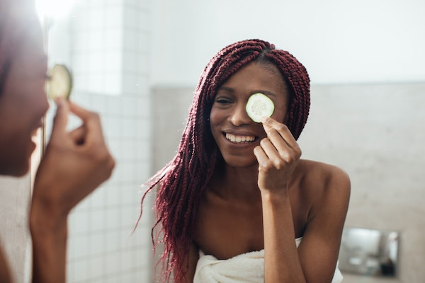 A young woman poses in the mirror at a spa, while wearing a bath towel and holding a cucumber slice over her eye.
