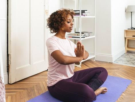 A woman sits with her hands in prayer pose before doing a yoga youtube video for when you don't feel like going to class