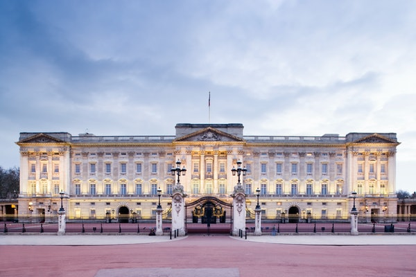 Buckingham Palace lights up as the sun sets in London, England.