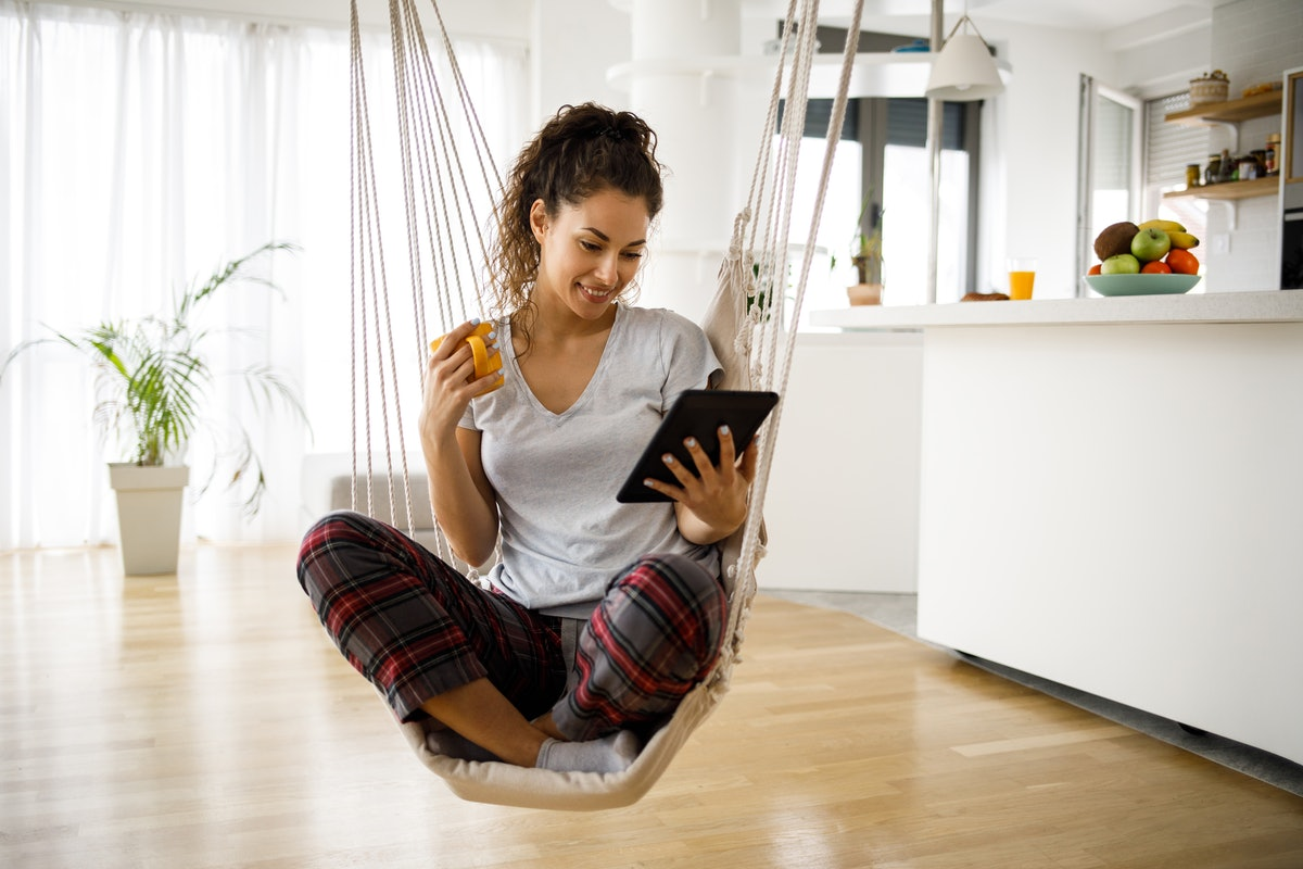 A young woman sits in a rope swing in her home while looking at her iPad.