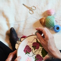 A woman embroiders strawberries onto plain fabric. These 9 DIY projects help when you're sad and need a pick me up