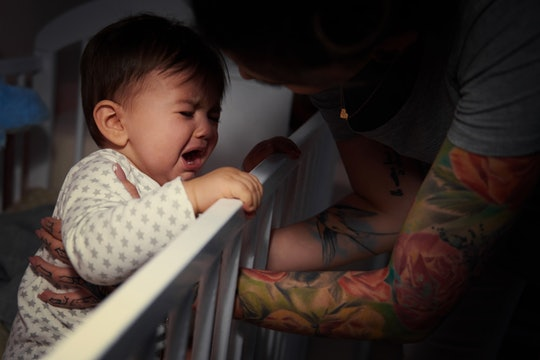 mom comforting crying baby in crib