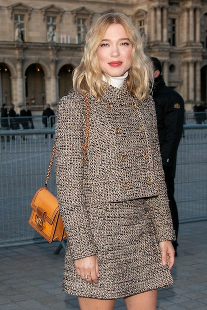 Lea Seydoux wears a rosy pink lipstick and tweed skirt and blazer outside of the Louis Vuitton show ...