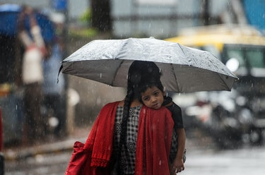 A mom in India carries her little boy through the rain.