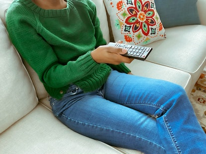 A woman watches TV in order to distract herself from her coronavirus anxiety.