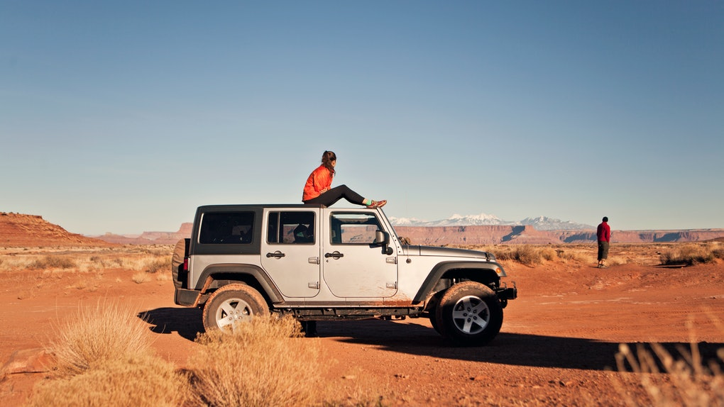 A woman sits on a white jeep in the middle of Canyonlands National Park.