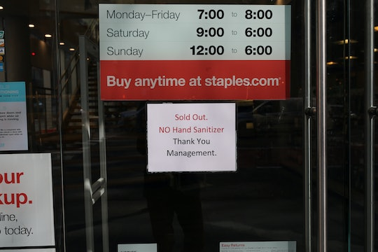 """a sign in a """"staples"""" window telling customers the store is sold out of hand sanitizer"""