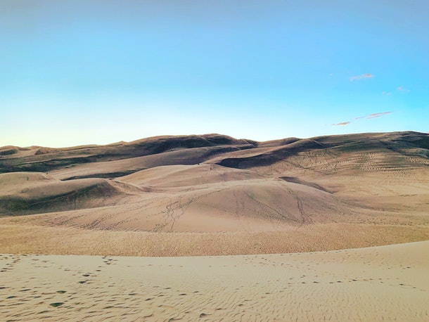 Great Sand Dunes National Park is covered in footprints on a sunny day.