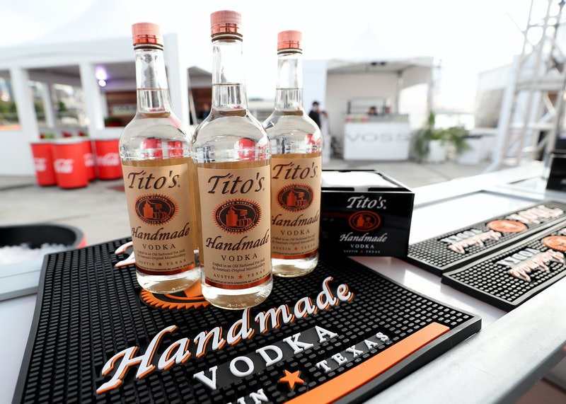Three bottles of Tito's Vodka stand on an outdoor bar. Tito's Vodka has issued a statement to its consumers, saying that using vodka to make homemade hand sanitizer to fight coronavirus is not helpful.