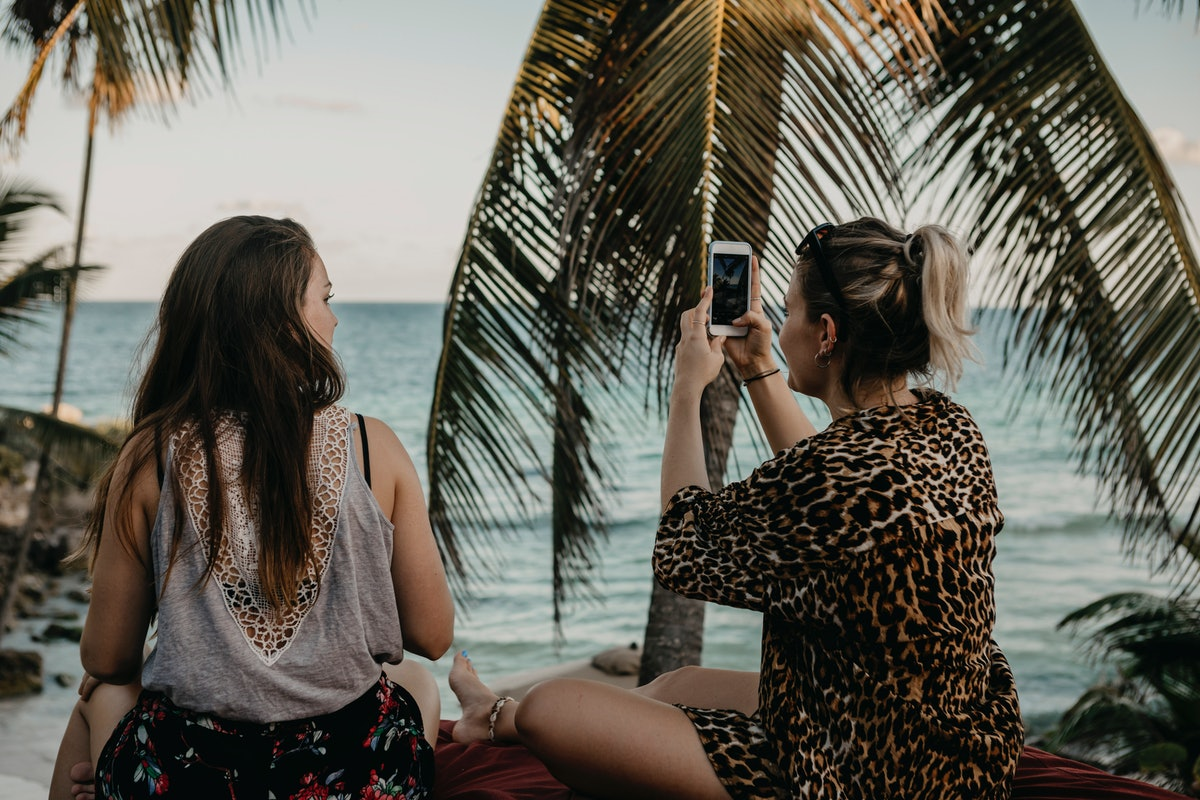 Two girls sit and look at the ocean while on spring break in Mexico.