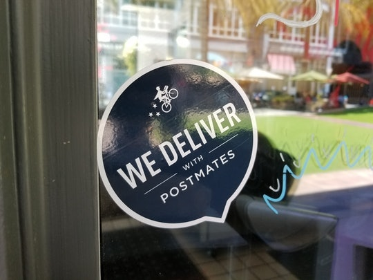 a postmates sticker in the window of a restaurant