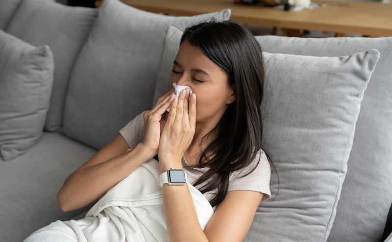 A person in a white shirt lays in bed and blows her nose. Spring allergies can definitely feel much ...