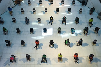 Food delivery drivers sit on chairs spaced apart for social distancing, as part of the effort to contain the COVID-19 coronavirus, as they wait for takeaway orders at Central Pinklao shopping mall in Bangkok, Thailand 28 March, 2020.
