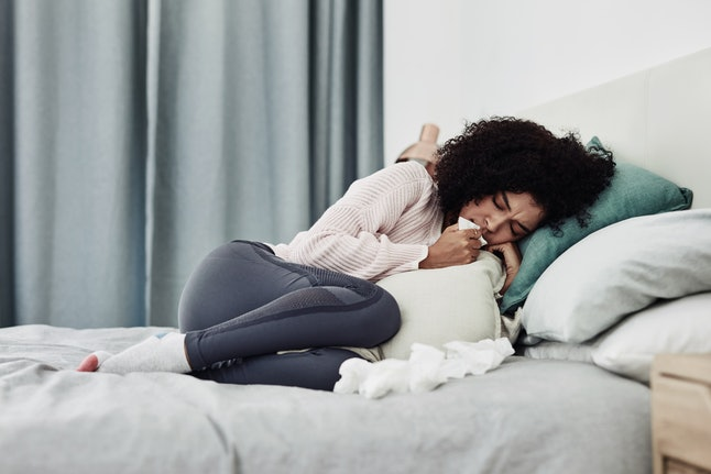 A woman surrounded by tissues in bed. If your spring allergies get worse at night, you're not alone