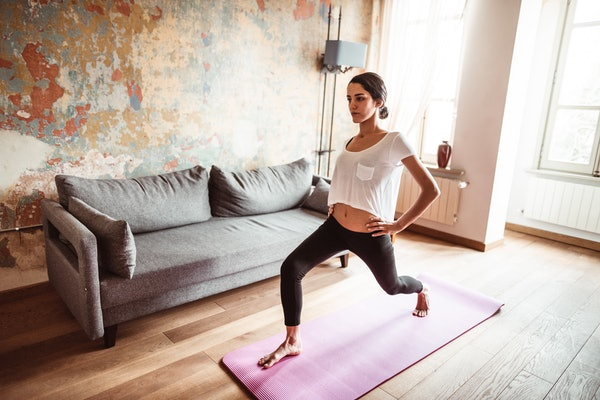 A young woman does yoga on a pink mat in the living room of her home.
