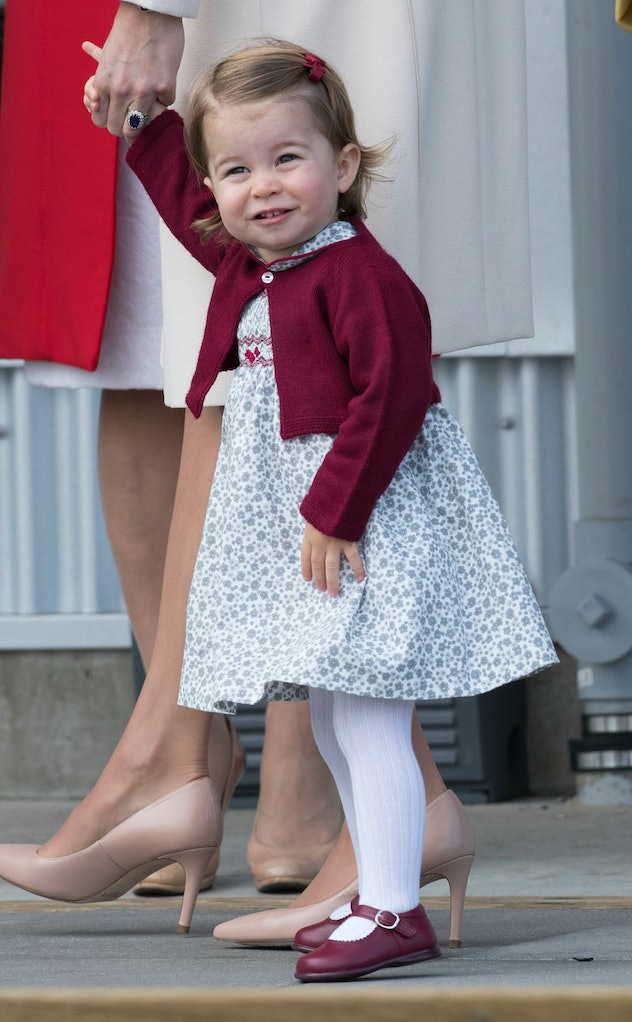 Princess Charlotte smiles while holding her mom's hand