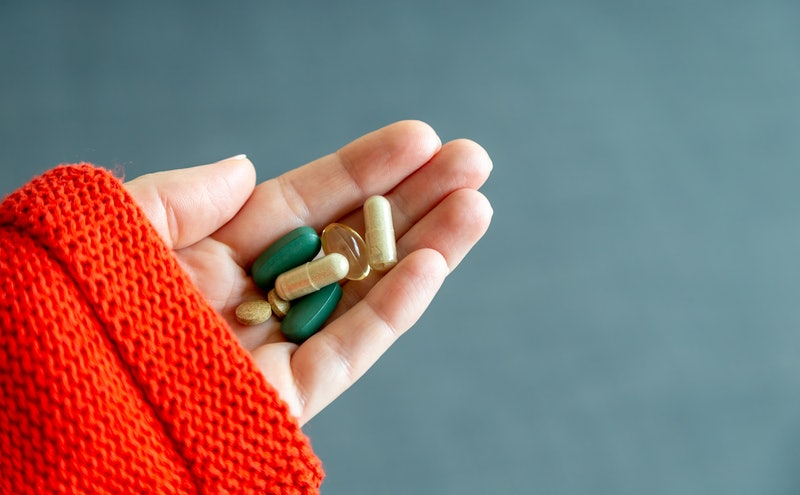 A woman holds a handful of pills. Immunity-boosting supplements won't do anything for coronavirus, doctors say